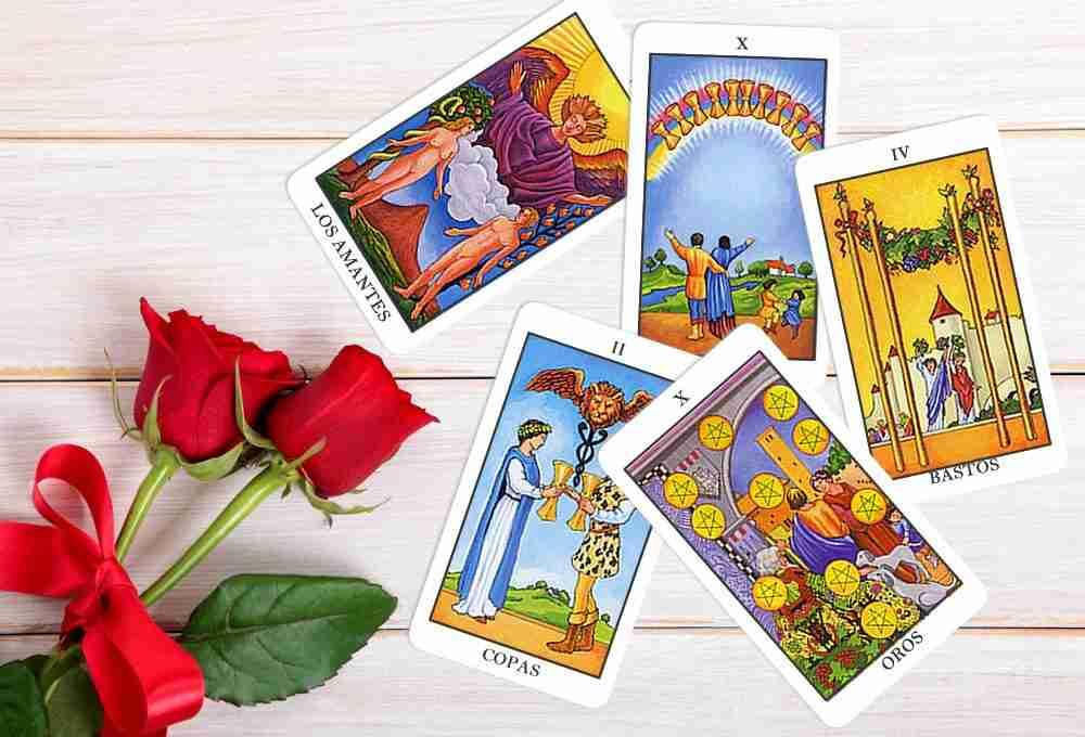 Cartas de Tarot - Os Amantes 6, 10 de Ouros, 2 de Copas, 10 de Copas e 4 de Paus. Duas rosas vermelhas.