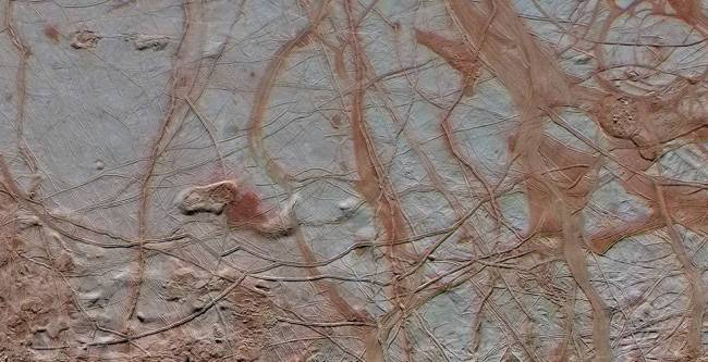 "The surface of Europa. Darker ""stains"" in cracks are thought to be residue from material which has come up to the surface from the ocean below. Image Credit: NASA/JPL-Caltech/SETI Institute"
