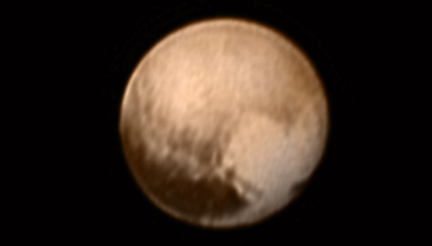 "The newest image of Pluto, taken by New Horizons' Long Range Reconnaissance Imager (LORRI) camera less than six days before closest approach. The long dark area called the ""whale"" is in the lower left and the brighter ""heart"" region is in the lower right. Image Credit: NASA/JHUAPL/SWRI"