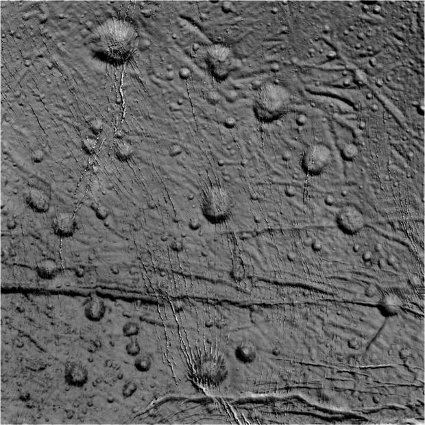 Raw image from the Oct. 14 flyby, showing craters and cracks in the icy surface. Image Credit: NASA/JPL-Caltech/Space Science Institute