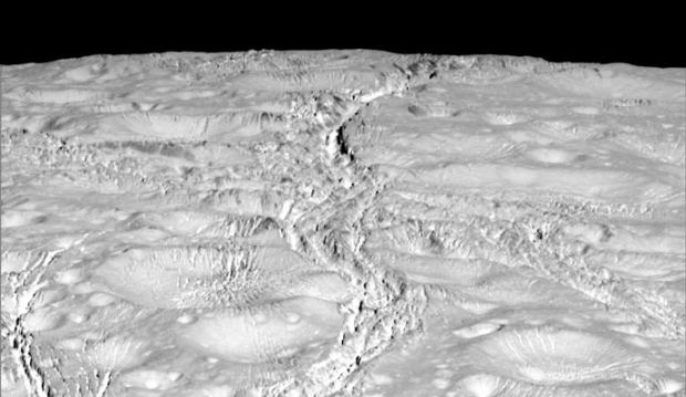New high-resolution view of the north polar region on Enceladus, showing a cratered surface crisscrossed by many cracks. Image Credit: NASA/JPL-Caltech/Space Science Institute