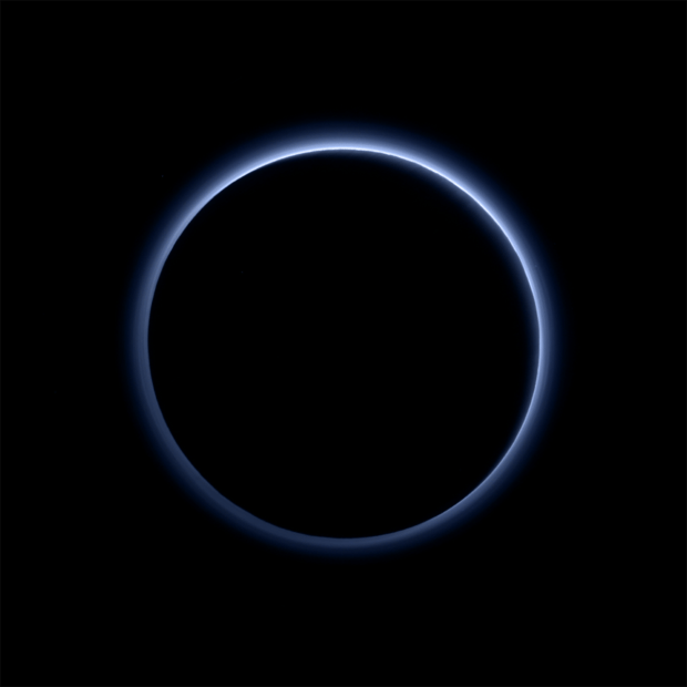 The blue skies of Pluto, as seen in this image from New Horizons. Pluto is backlit by the Sun, revealing the multilayered hazes in the atmosphere. Soot-like particles in the atmosphere scatter sunlight in a way that the atmosphere appears blue, similar to what happens on Earth. Image Credit: NASA/JHUAPL/SwRI