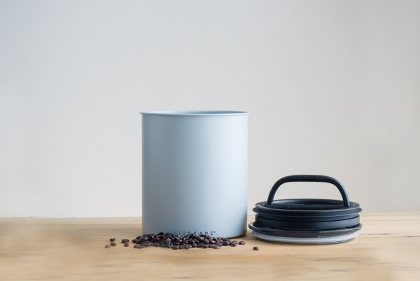 Photo of matte grey Airscape Kilo (large) with lid and seal to the right side and coffee beans in front on counter