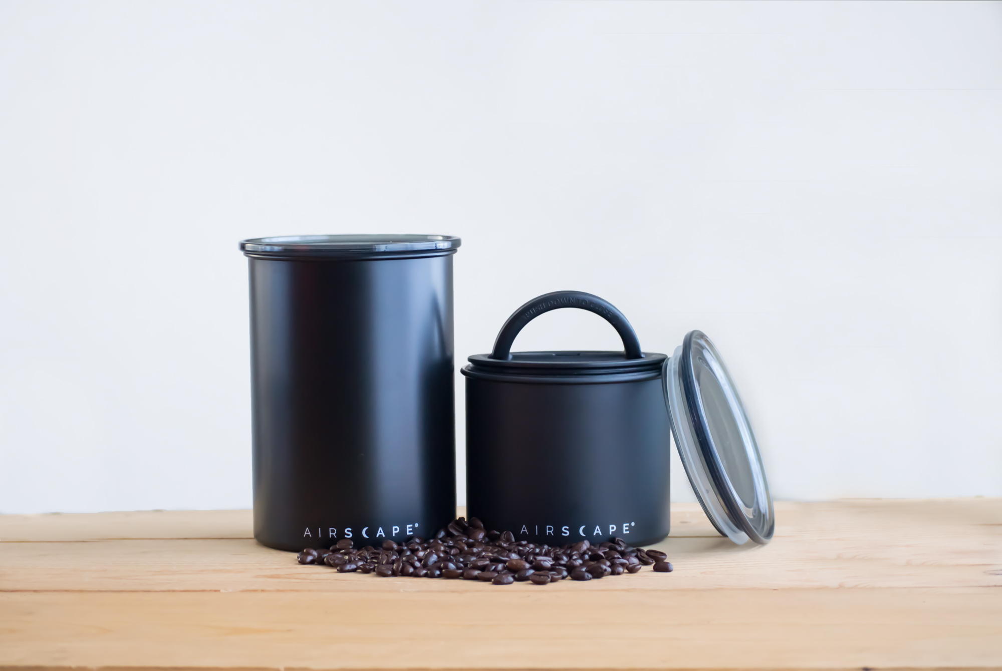 Photo of matte black Airscape small and medium kitchen canisters on counter