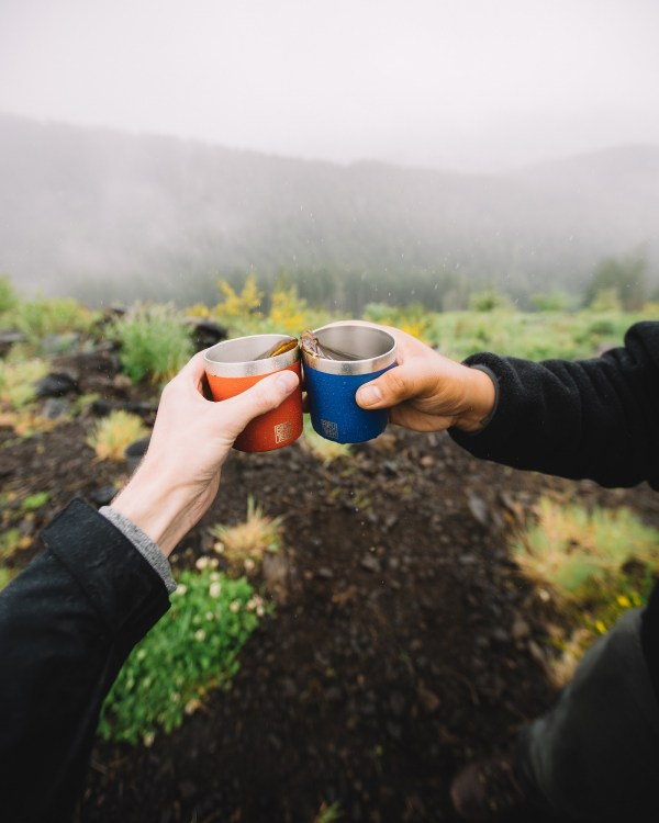 """Photo of two hands each holding a BruTrek Camp Cup with coffee in them, giving each other a """"Cheers!"""""""