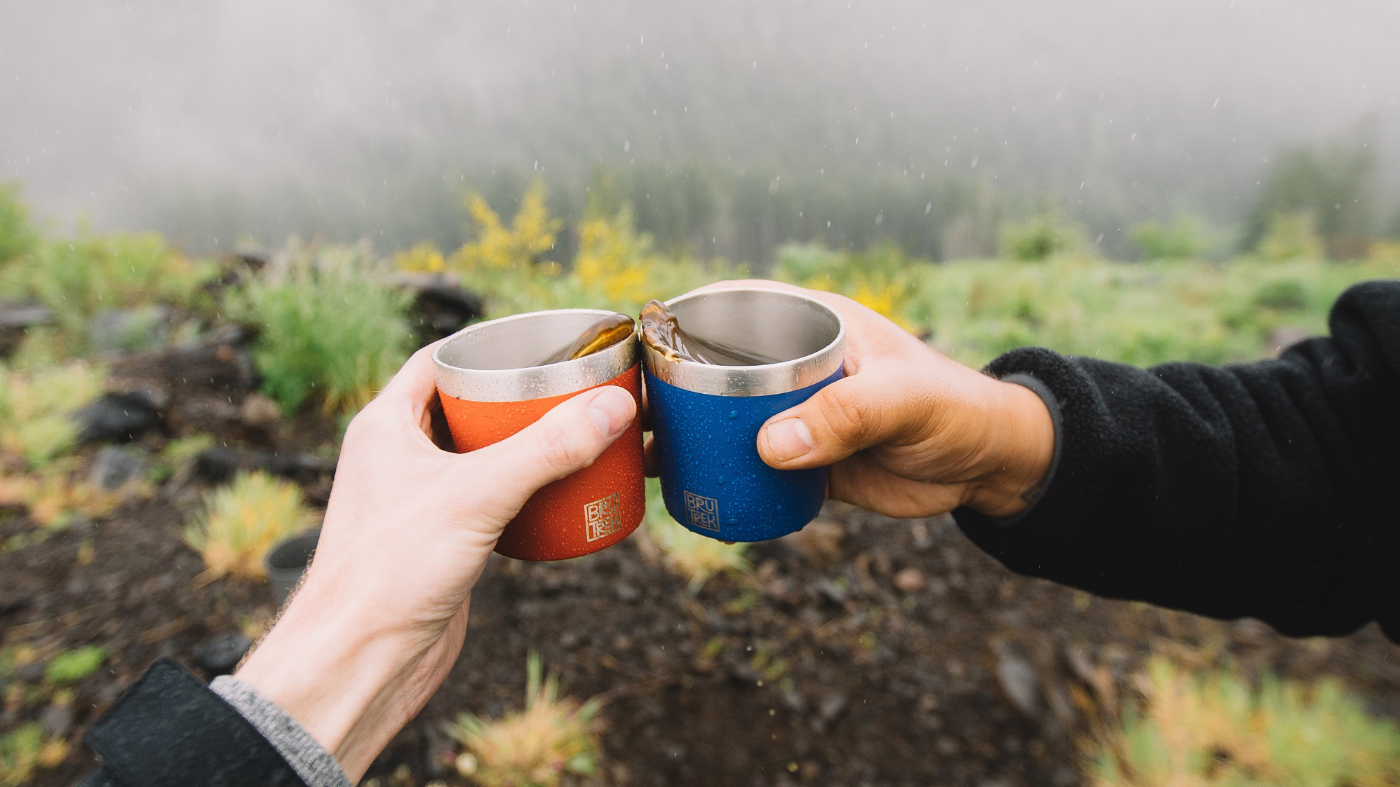 """Photo of two hands holding BruTrek camp cups and giving each other a """"cheers"""""""