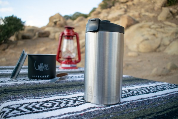 Photo of an insulated BruTreck coffee mug sitting on a covered picknick table with a lantern in the background.