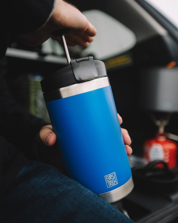 Photo of someone sitting inside a vehicle while pressing down on a blue colored coffee press plunger.