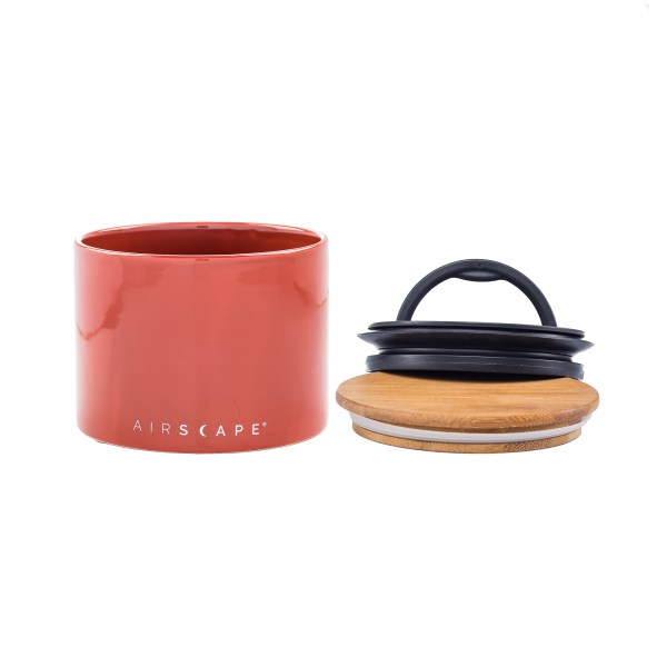 Photo of small Red Rock color Airscape Ceramic with bamboo lid and innner seal lid sitting next to canister