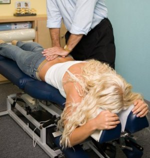 chiropractor laying hands on sacral spine