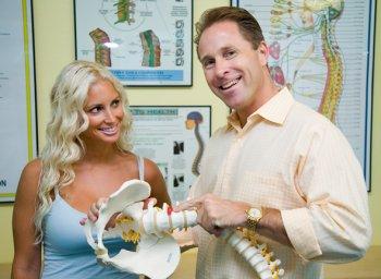 Chiropractor Michael Dorausch demonstrating lumbar disc herniation on spinal model