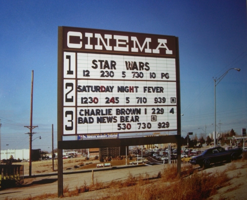 Outdoor movie sign promoting Star Wars and Saturday Night Fever