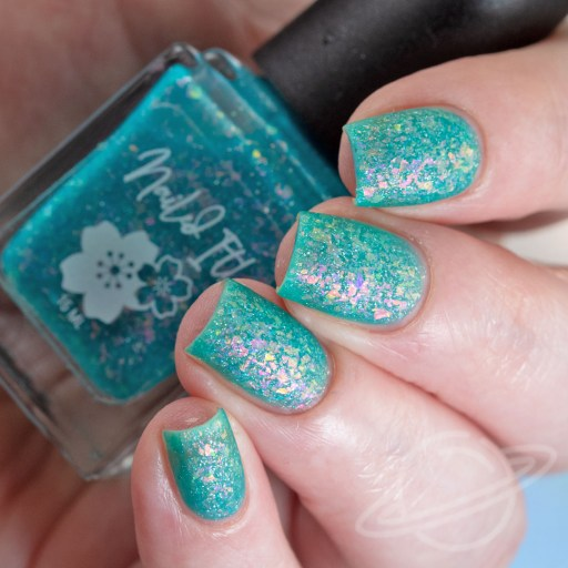 4 Finger nail swatch of Bedtime Blues a sheer turquoise jelly packed with violet/pink/gold/crystal flakies, and a touch of holo micro flakies nail polish by brand Nailed It from The Charity Box Book Club February 2021 Matte