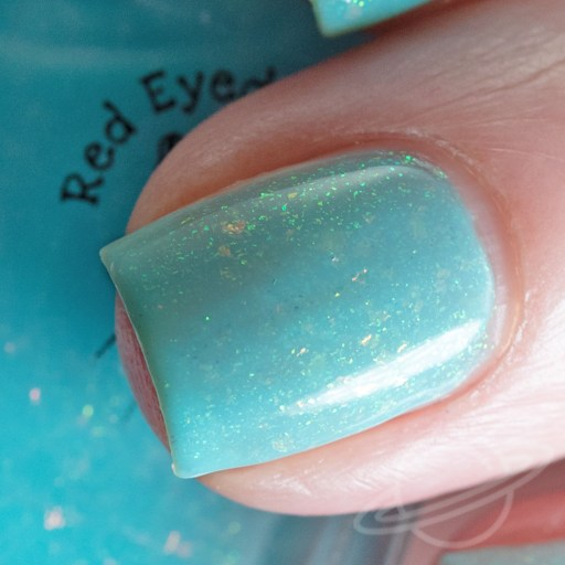 One finger nail macro swatch of Fold In The Cheese is a bright sky blue crelly with green/gold shifting shimmer and pink/gold/orange shifting flakies by Red Eyed Lacquer