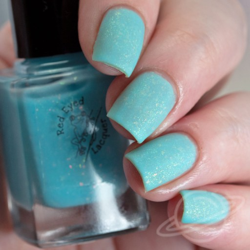 Four finger nail swatch of Fold In The Cheese is a bright sky blue crelly with green/gold shifting shimmer and pink/gold/orange shifting flakies by Red Eyed Lacquer MATTE
