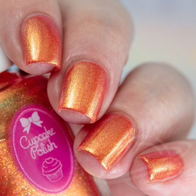 Pictured here is a four finger nail swatch of Cupcake Nail Polish Rum Swizzle a red nail polish packed with green to gold iridescent aurora shimmers photographed in artificial daylight bulbs