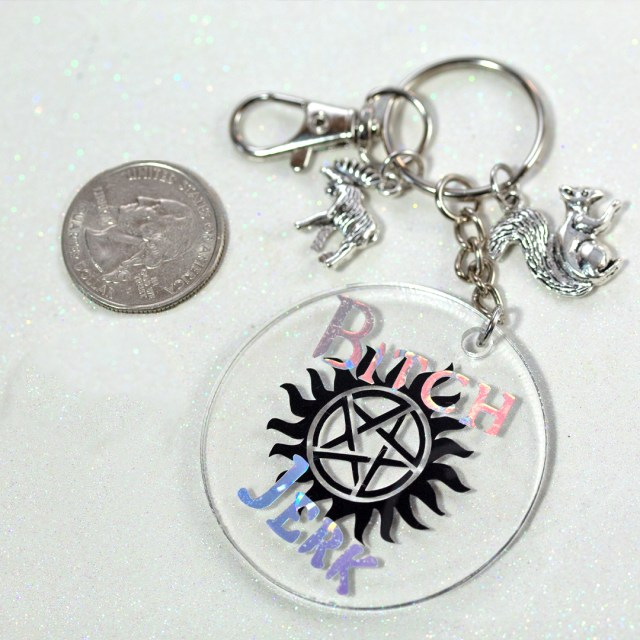 Keychain inspired by Supernatural. Created by Fan Girl Polish. Clear medallion with Supernatural Logo and two charms, one a moose and the other a squirrel. Part of The Very Supernatural Collab