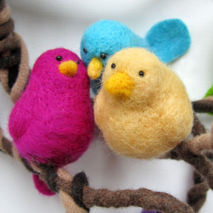 pink, blue and yellow needlefelt birds on a branch