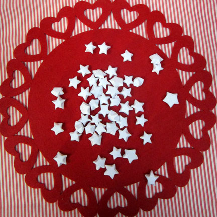 origami stars on red mat Origami Stars -  Day three Planet Penny Advent Calendar