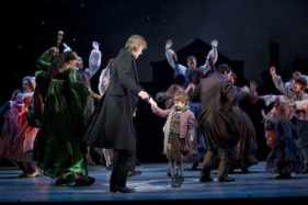 Graeme Malcolm (Scrooge) and Noah Hinsdale (Tiny Tim) with the full company of A Christmas Carol. Photo by T Charles Erickson.