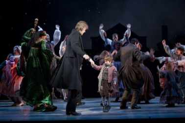 Graeme Malcolm (Scrooge) and Noah Hinsdale (Tiny Tim) with the full company of A Christmas Carol. Photo by T Charles Erickson, courtesy of McCarter Theatre.