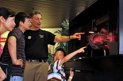 PPPL Science Writer John Greenwald explains some of the basic principles of fusion to visitors at the fusion demonstration machine.
