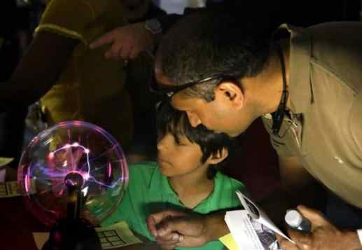 Prasad Chalasani, of Princeton Junction, and his son, Avinash, 8, examine a plasma ball in the Science Education Laboratory at the Princeton Plasma Physics Laboratory's Open House. Photo: Elle Starkman/PPPL Office of Communications.
