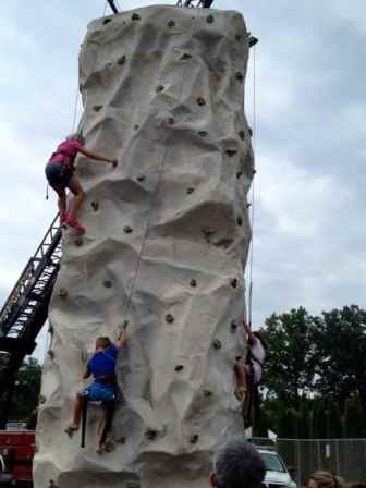 Kids climb a rock wall at the 2013 National Night Out in Princeton.