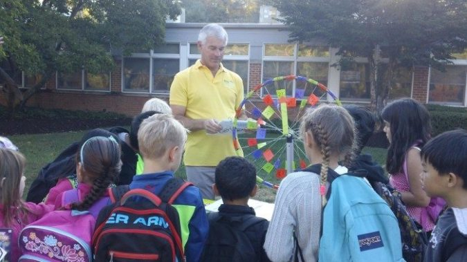 Jerry Foster from the Greater Mercer Transportation Management Association with students at this morning's Johnson Park Elementary School event. Foster is showing quizzing students about  bike and walk safety.