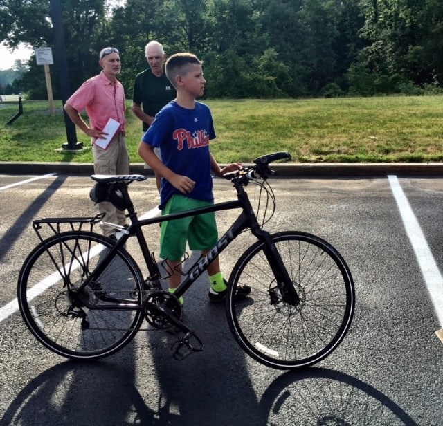 Henry Garnich helps his dad, Pete Garnich or Knapp's Cyclery, load a bike on a truck Thursday.