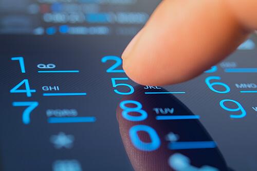 Finger on phone keypad