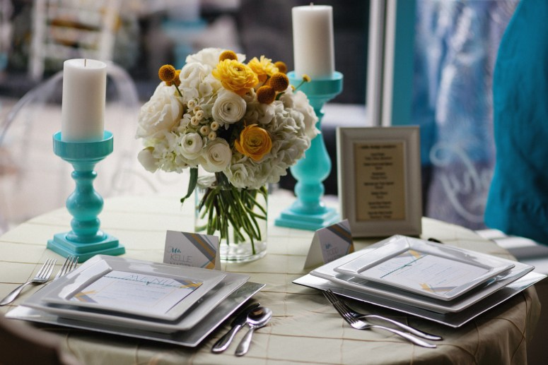 wedding centerpiece with white, yellow, and teal