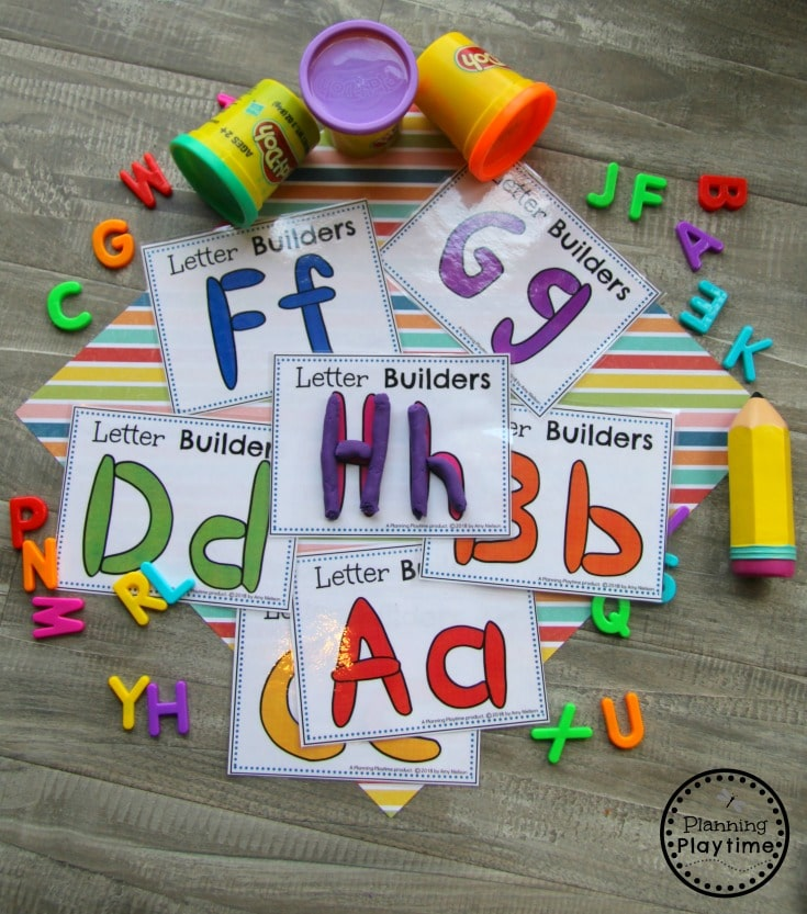 Alphabet cards on a table with playdough cans. Playdough rolled and shaped to letters on cards.