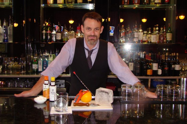Christ Norton stands before hand carved block of ice and ingredients for specialty Frisco cocktail