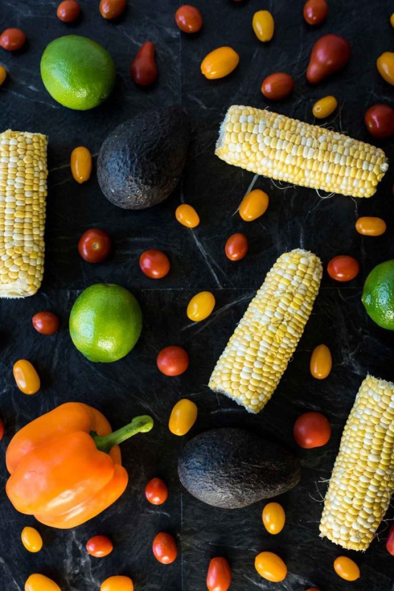 Black bean corn salad ingredients on a black marble background. There are 4 ears of corn, an orange bell pepper, cherry tomatoes, and a few limes.