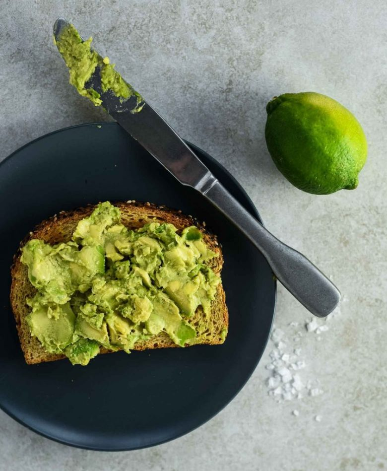 Vegan avocado toast. Avocados getting smashed and smeared on whole wheat toast on blue plate. There is a lime and salt to the right with a dirty knife on the plate.