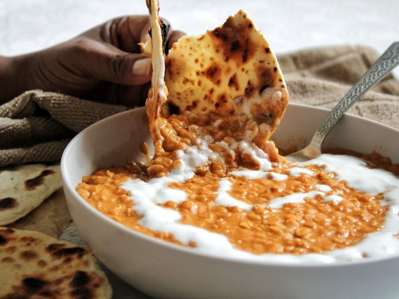 Dipping naan in a bowl of peanut butter red lentil curry