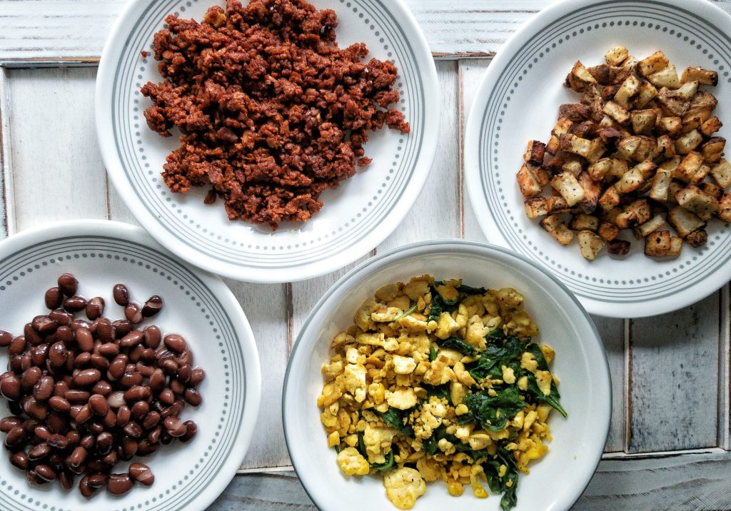 White plates with cooked soyrizo, potatoes, beans, and tofu scramble with greens