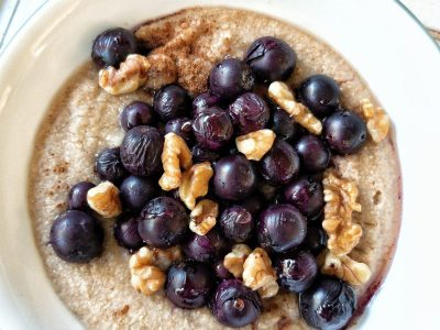 Bowl of creamy oat bran topped with grapes and walnuts