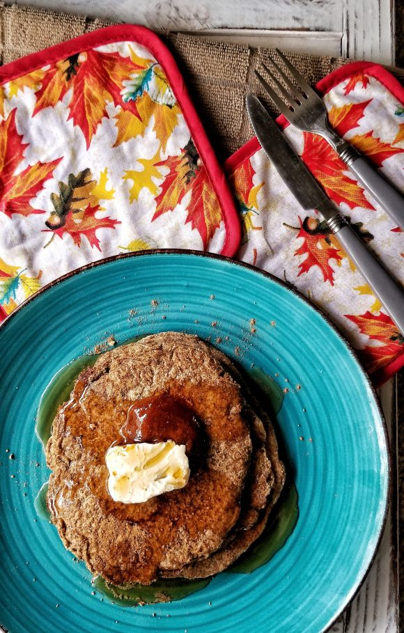 Stack of oat bran pancakes with a dollop of vegan butter and a pour of syrup.