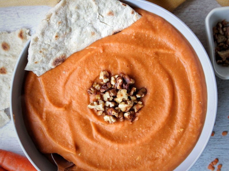 Soup made with lentils, carrots, and ginger served with a homemade flatbread