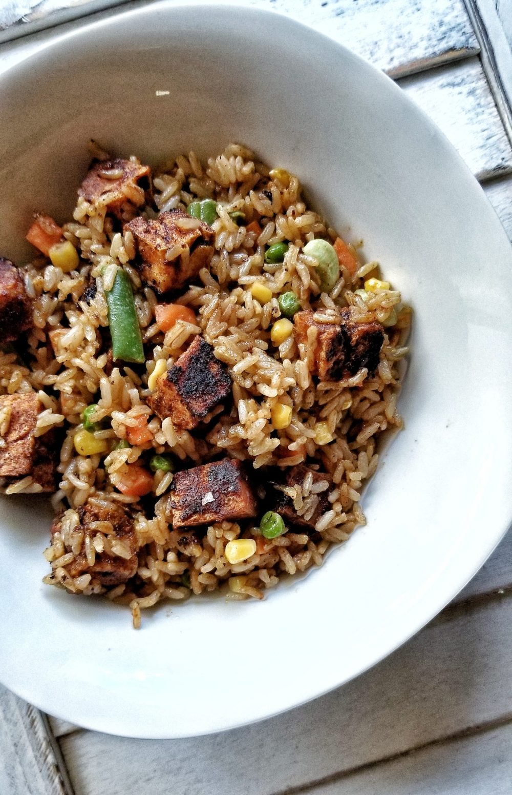 Bowl of stir-fried rice with tofu and mixed vegetables