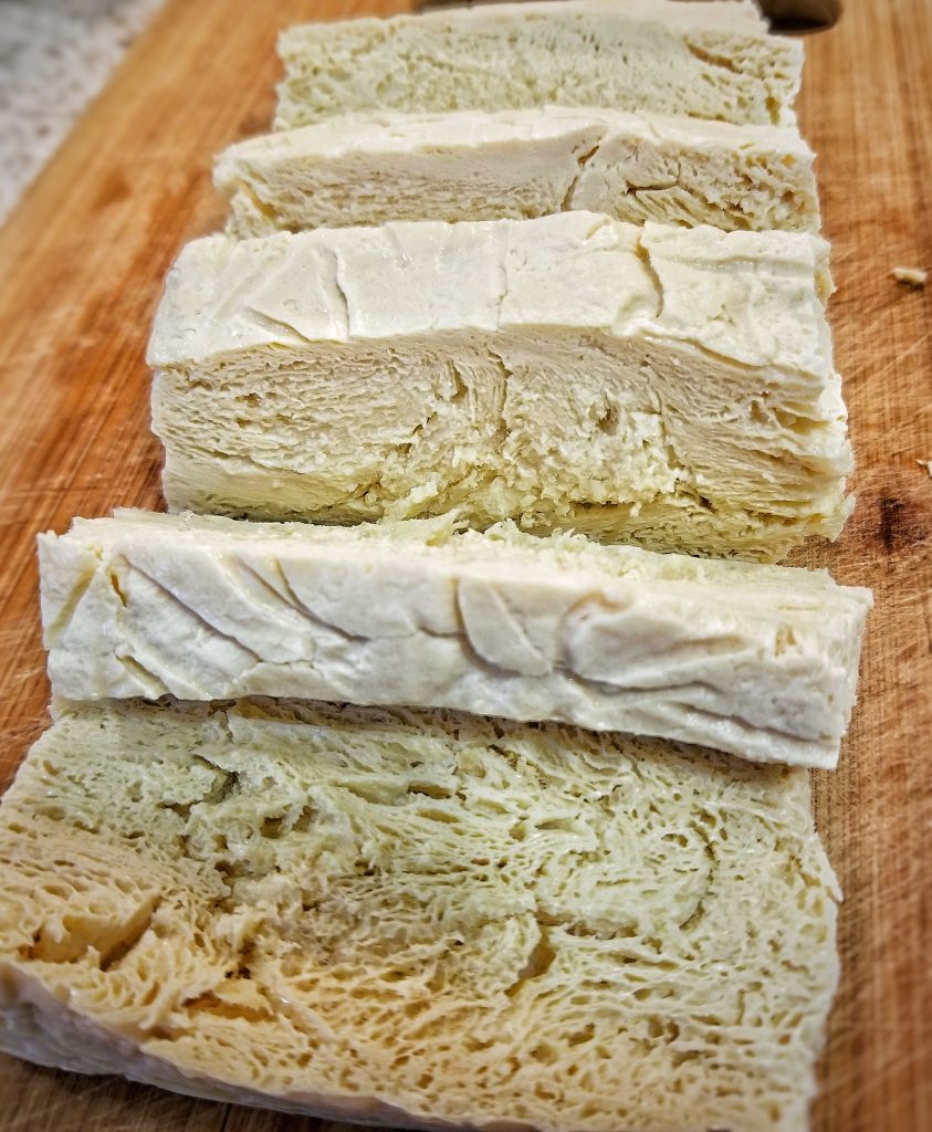 Slabs of tofu showing the pourous inside from being frozen and then thawed