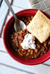 Bowl of vegan mushroom chili with vegan sour cream and cornbread