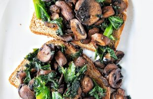 Two slices of whole wheat toast topped with cooked mushrooms and kale