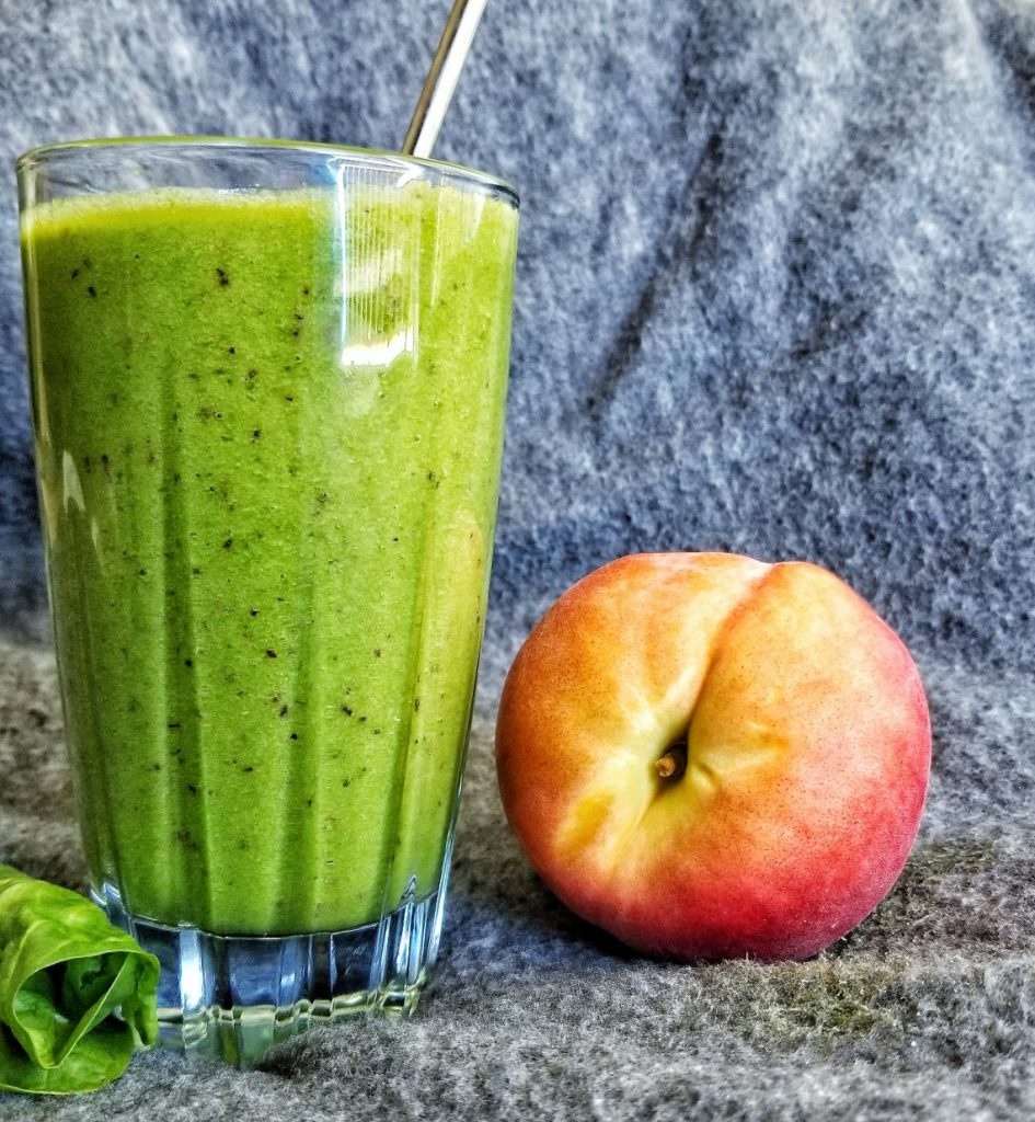 Green smoothie with frozen fruit including peaches and bananas.