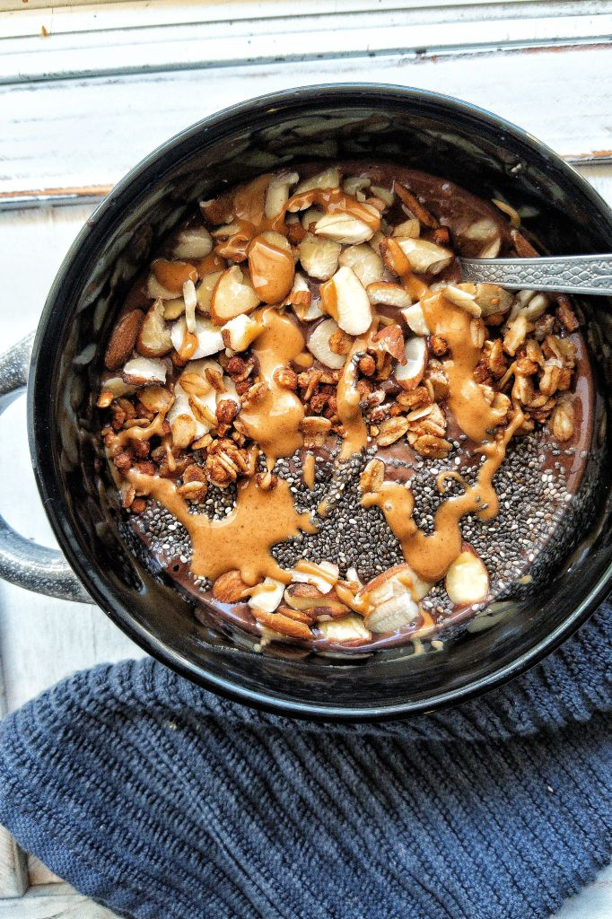 A chocolate banana smoothie bowl snack topped with peanut butter, chia seeds, sliced almonds, and granola