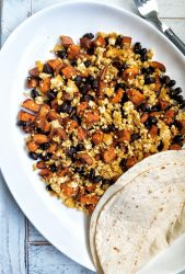 Tofu scramble made with sweet potato, black beans, and spices. With a side of tortillas.