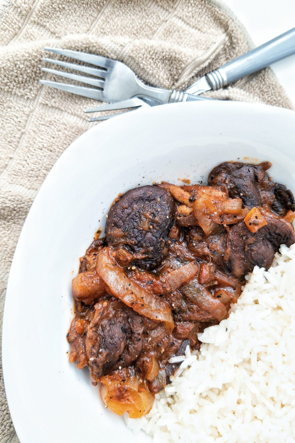 Stewed mushroom with onion and a side of rice in a bowl
