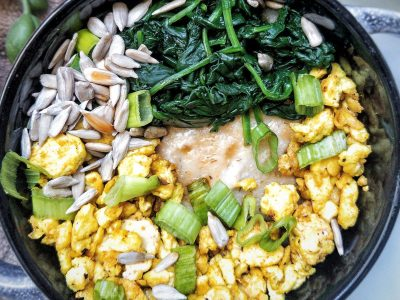 Bowl of creamy oat bran topped with tofu scramble, steamed spinach, sunflower seeds, chopped green onions, and a drizzle of soy sauce